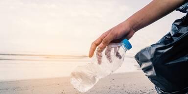Beachcleaning Mann hebt Plastikflasche auf