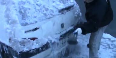 Mann enteist Auto mit einem Hammer
