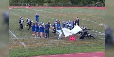 Football-Team läuft gegen Banner
