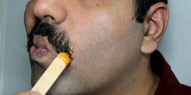 Mann brennt sich Schnurrbart ab