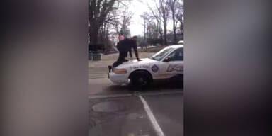 Mann läuft über Polizeiauto