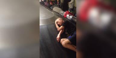 Mann schläft auf Kofferband