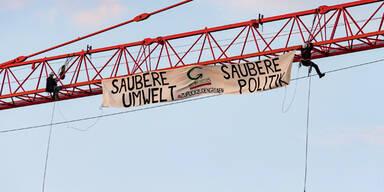 Die Grünen Wien entrollen Banner auf Baukran über Parlament