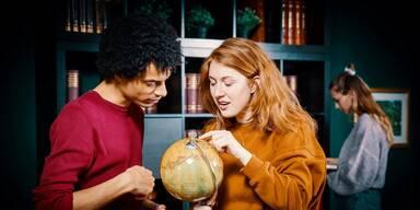 Secret Study Locks & Clocks - Ein Mann und eine Frau schauen sich einen Globus an