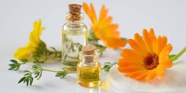 Ringelblumen orange und gelb liegend auf Wattepads neben Fläschchen mit ätherischem Öl.