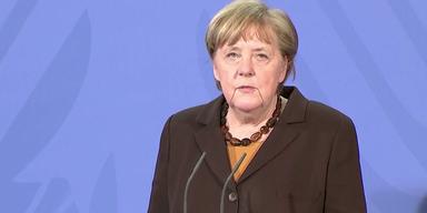 Bundeskanzlerin Angela Merkel vor blauem Hintergrund