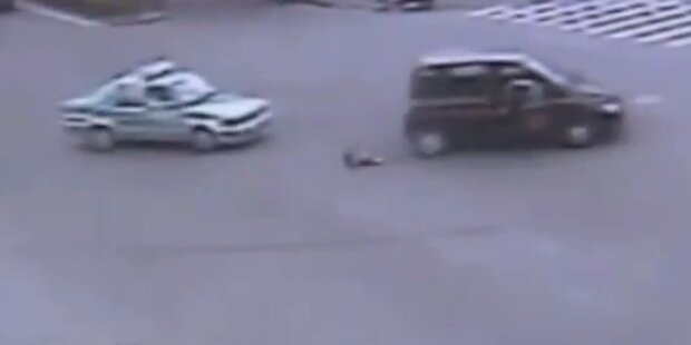 Kind fällt aus fahrendem Auto auf Straße