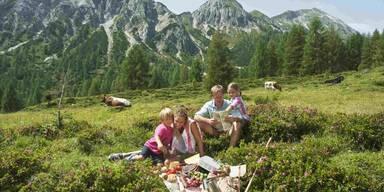 Familie macht Picknick in den Bergen
