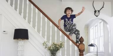 Junge steht auf dem Treppengeländer