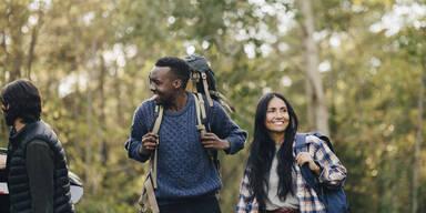 Drei junge Menschen, die im Wald unterwegs sind