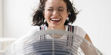 Frau vor Ventilator, lachend
