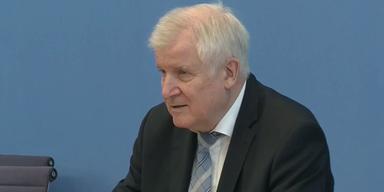 Horst Seehofer bei Pressekonferenz vor blauem Hintergrund