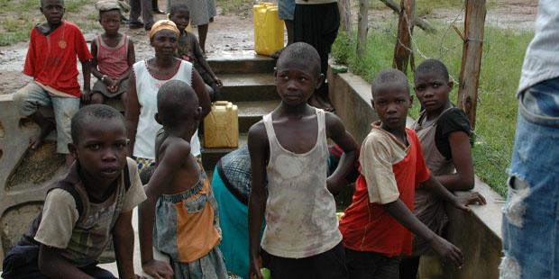 Kinder in Uganda mit Wasserbehältern.