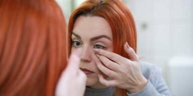 Rothaarige Frau setzt sich vorm Spiegel eine Kontaktlinse ein.
