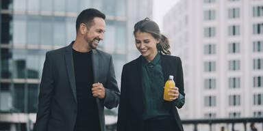 Lächelnder Mann und Frau im Business Outfit am reden