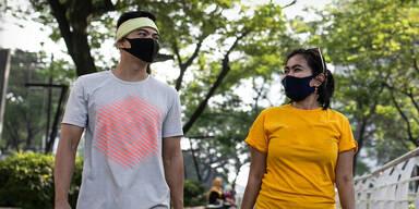 Menschen mit Maske beim Spazieren im Freien