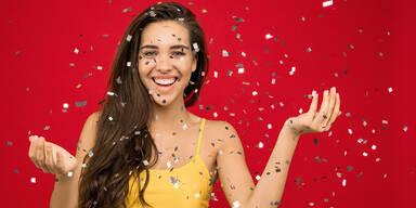 Junge Frau mit langen braunen Haaren lachend vor rotem Hintergrund.