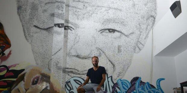 Künstler boxt Mandela-Portrait an Wand