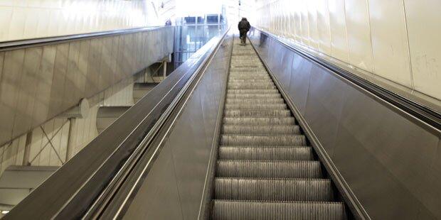 Mann tritt auf Frau auf U-Bahn-Rolltreppe ein