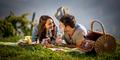 Frau und Mann picknicken im Weingarten