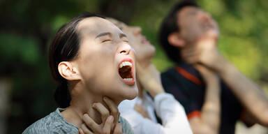 Menschen im Wald schreien und halten sich den Hals