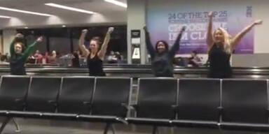 Irre Frauen tanzen am Flughafen