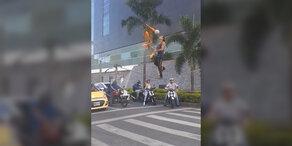 Irrer Akrobat tanzt über Straße