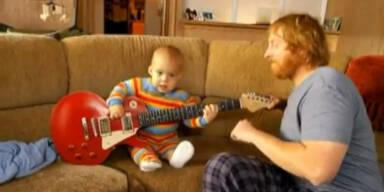 Babymozart spielt mit Vater Gitarre