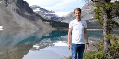 Simon's Reisen - Simon vor einer Berglandschaft mit See
