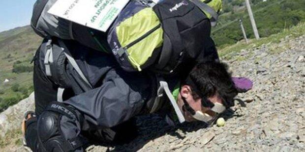 Kerl stupst mit Nase Kohlsprosse Berg hoch