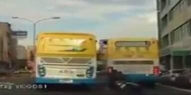 Unverletzt! Verrückter Biker rutscht unter Bus