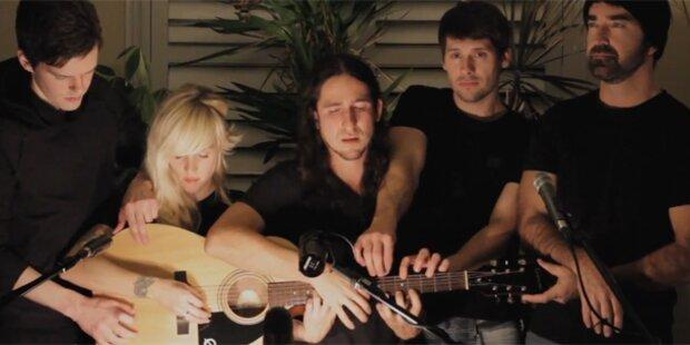 Fünf Musiker spielen auf einer Gitarre
