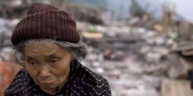 Eine Frau vor den Trümmern ihrer Existenz