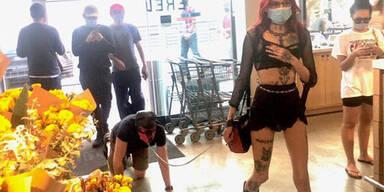 Domina geht mit Masken-Mann an der Leine einkaufen
