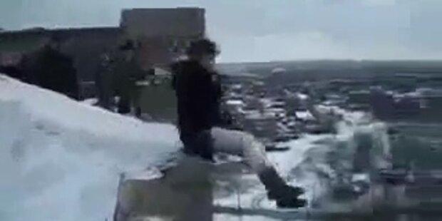 Russen springen mit Rodel vom Dach