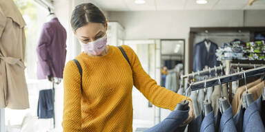 Frau mit Maske in einem Bekleidungsgeschäft
