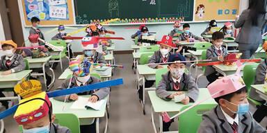 """Kinder tragen """"Ein-Meter-Hüte"""" in chinesischer Volksschule"""