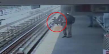 Kinderwagen rollt auf Bahngleise - Zug naht