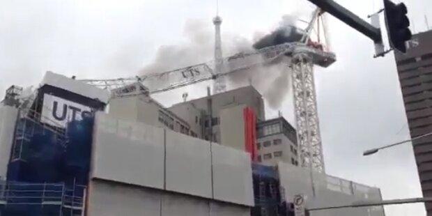 Brennender Kran kracht auf Gebäude