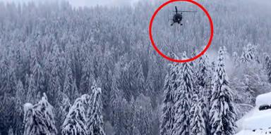 Hubschrauber blasen Schnee von Bäumen