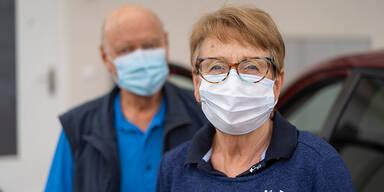 Altes Ehepaar mit Maske im Freien