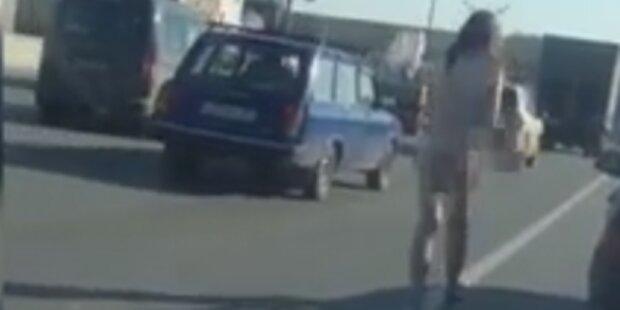 Nackte Frau geht auf Autobahn herum