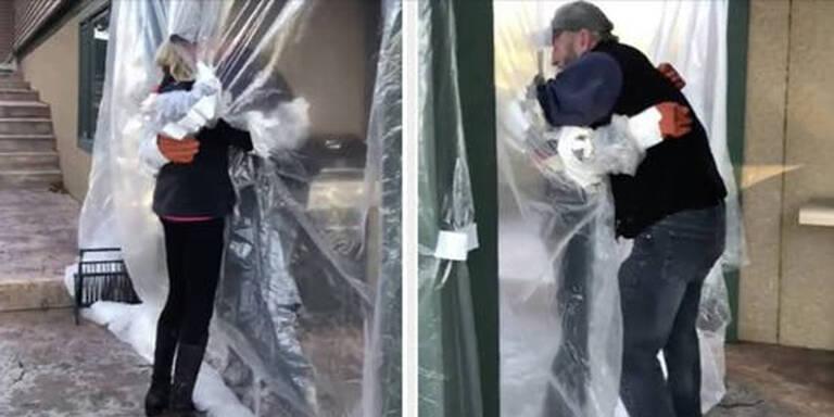Trauernde umarmen sich durch Plastik-Vorhang