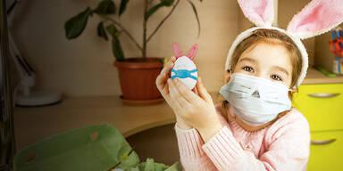 Kind mit Maske, Hasenohren und Osterei
