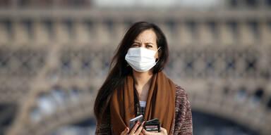 Frau vor Eiffelturm mit Maske