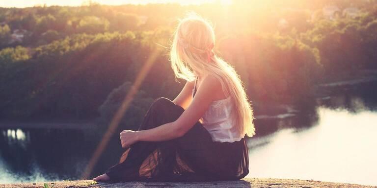 Dame sitzt auf einem Holz und schaut auf einen Fluss.