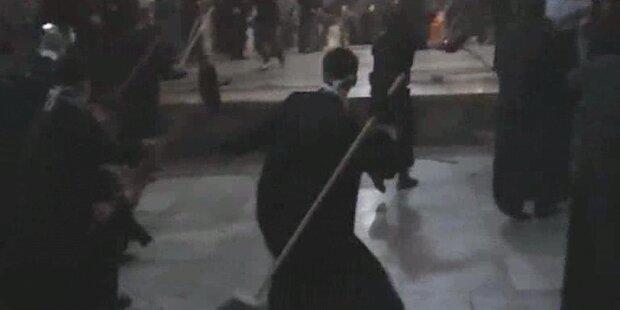 Priester prügeln sich mit Besenstielen