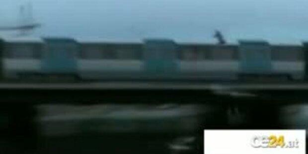 Mann springt von fahrendem Zug