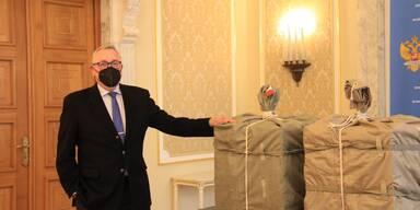 Mitarbeiter der russischen Botschaft mit Sputnik V-Paket