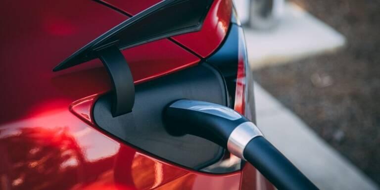 Elektrotanköffnung beim Betanke eines roten Teslas.
